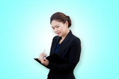 Donna di affari asiatica che scrive una nota fotografia stock libera da diritti
