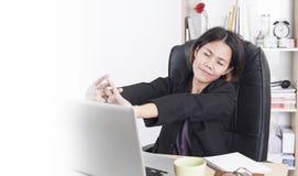 Donna di affari asiatica che si siede al computer della tavola in ufficio Immagini Stock
