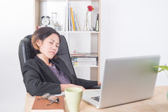 Donna di affari asiatica che si siede al computer della tavola in ufficio Immagine Stock Libera da Diritti