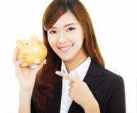 Donna di affari asiatica che tiene un porcellino salvadanaio dorato Immagine Stock