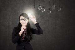 Donna di affari asiatica con una lampadina Fotografia Stock
