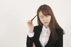 Donna di affari asiatica sollecitata con una penna Fotografia Stock