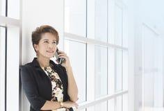 Donna di affari asiatica sul telefono in ufficio Fotografia Stock