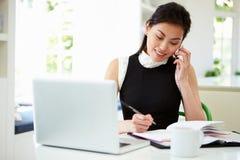 Donna di affari asiatica Working From Home che per mezzo del telefono cellulare Immagini Stock