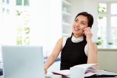Donna di affari asiatica Working From Home che per mezzo del telefono cellulare Fotografia Stock Libera da Diritti