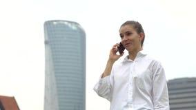 Donna di affari astuta della città che parla su un telefono cellulare archivi video