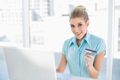 Donna di affari astuta sorpresa che compera online Fotografie Stock