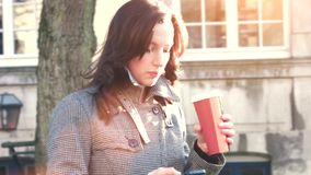 Donna di affari attraente all'aperto con il telefono cellulare ed il caffè archivi video