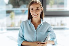 Donna di affari attraente allegra che tiene il suo smartphone immagini stock libere da diritti