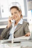 Donna di affari attraente che comunica sul sorridere del telefono Immagini Stock