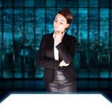 Donna di affari attraente che esamina un grande schermo bianco Immagini Stock