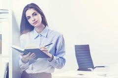 Donna di affari attraente che fa le note mentre stando Fotografie Stock