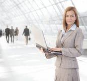 Donna di affari attraente che per mezzo del computer portatile al passaggio Fotografia Stock