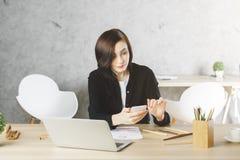 Donna di affari attraente che per mezzo dello smartphone nel luogo di lavoro Fotografia Stock Libera da Diritti