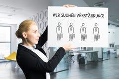 """Donna di affari attraente che tiene un segno con il messaggio """"che stiamo assumendo """"in tedesco fotografie stock libere da diritti"""