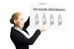 """Donna di affari attraente che tiene un segno con il messaggio """"che stiamo assumendo """"in tedesco immagine stock"""