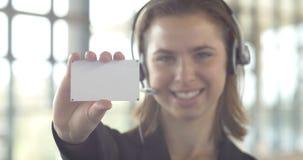 Donna di affari in bianco del biglietto da visita con la tenuta della cuffia avricolare nell'ufficio video d archivio