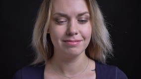 Donna di affari bionda di mezza età felice in orologi blu della blusa allegro nella macchina fotografica su fondo nero stock footage