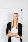 Donna di affari bionda sorridente con le armi piegate Fotografie Stock Libere da Diritti