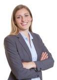 Donna di affari bionda in una giacca sportiva con le armi attraversate Fotografia Stock Libera da Diritti