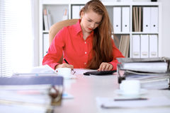 Donna di affari in blusa rossa che stendere rapporto, calcolatrice o controllante equilibrio Immagine Stock Libera da Diritti