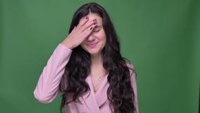 Donna di affari castana nel facepalm allegro di gesti rosa del rivestimento per mostrare disturbo divertente su fondo verde stock footage
