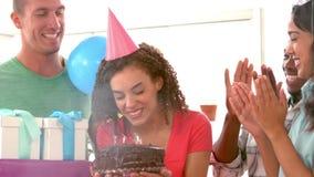 Donna di affari casuale che soffia la sua torta di compleanno stock footage