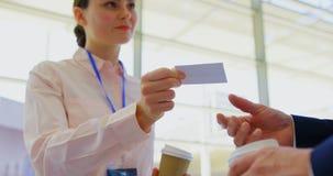 Donna di affari caucasica che dà una carta di visita ad un uomo d'affari nell'ingresso 4k dell'ufficio archivi video