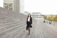 Donna di affari caucasica che sta sulle scale con la borsa e sulle alte costruzioni nel fondo Fotografia Stock