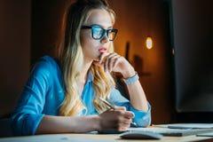 Donna di affari caucasica pensierosa in occhiali che scrive qualcosa con la matita e che si siede nel luogo di lavoro Immagine Stock Libera da Diritti
