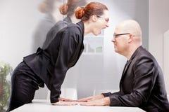 Donna di affari che affronta violentemente un uomo di affari Immagini Stock Libere da Diritti