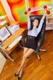 Donna di affari che allunga con i dumbbells Fotografie Stock