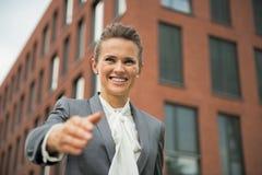 Donna di affari che allunga mano per la stretta di mano Immagine Stock