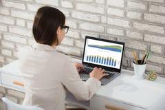 Donna di affari che analizza grafico sul computer portatile immagini stock