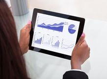 Donna di affari che analizza i grafici finanziari sulla compressa digitale Fotografia Stock