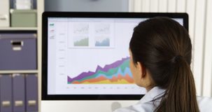 Donna di affari che analizza i grafici sul computer Immagine Stock Libera da Diritti