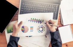 Donna di affari che analizza relazione di attività con i grafici ed il grafico Immagine Stock Libera da Diritti