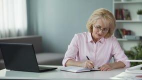 Donna di affari che annota al piano del taccuino per il prossimo avvenire, free lance archivi video
