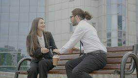 Donna di affari che ascolta il suo collega dell'uomo d'affari sul banco davanti alla costruzione corporativa mentre provando ad a video d archivio