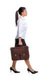Donna di affari che cammina con una cartella Immagine Stock