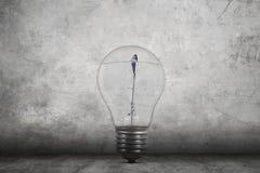 Donna di affari che cammina dentro la lampadina Fotografie Stock