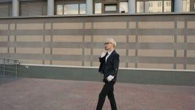 Donna di affari che cammina e che rende una telefonata all'aperto in città archivi video