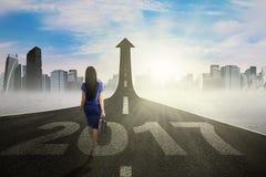 Donna di affari che cammina sulla strada con i numeri 2017 Immagine Stock