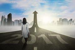 Donna di affari che cammina verso la freccia con 2017 Fotografia Stock Libera da Diritti