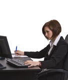 Donna di affari che cattura le note al suo scrittorio. fotografia stock