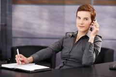 Donna di affari che cattura le note mentre sulla chiamata di telefono Fotografia Stock