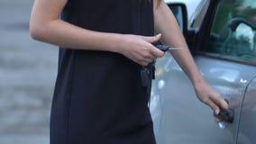 Donna di affari che chiude porta a chiave della sua automobile nel parcheggio, sistemi affidabili dell'allarme video d archivio