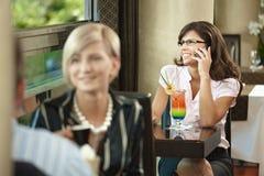 Donna di affari che comunica sul mobile in caffè Fotografia Stock