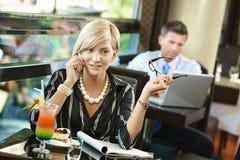 Donna di affari che comunica sul mobile in caffè Immagini Stock Libere da Diritti