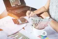 Donna di affari che conta soldi e che analizza rapporto finanziario del grafico con il calcolatore ed il taccuino sullo scrittori Immagine Stock